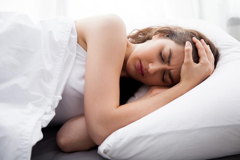 junge Frau mit Fieber im Bett liegend mit Decke bedeckt