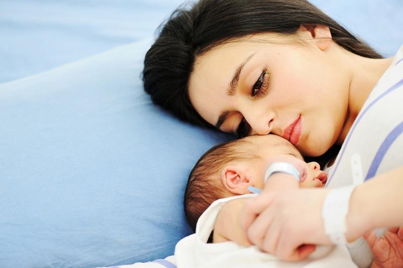 junge Frau mit Schmerzen auf dem Krankenhausbett mit ihrem Neugeborenen liegen