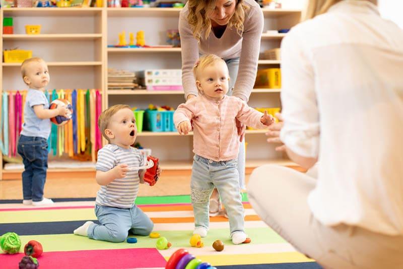 junge Frauen, die sich im Kindergarten um Babys kümmern