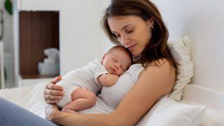 junge Mutter hält schlafendes Neugeborenes im Bett