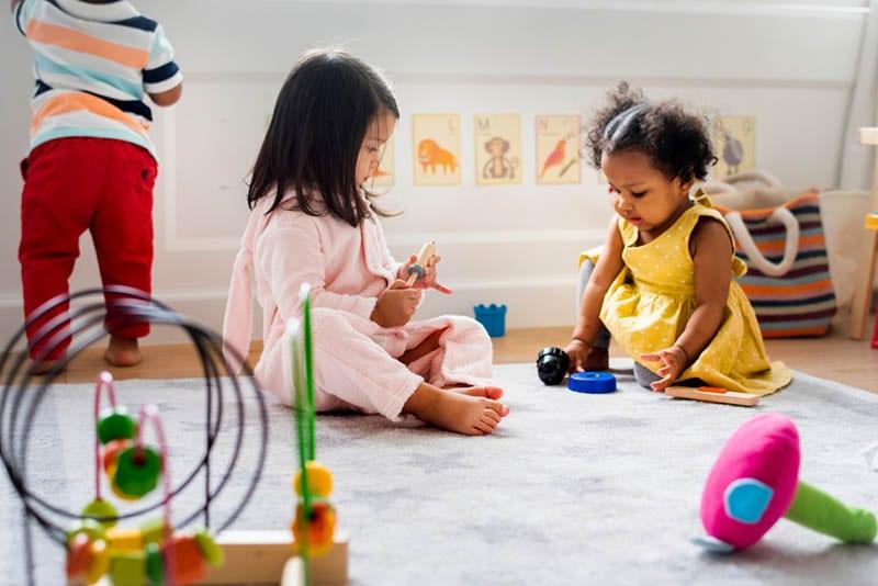 süße Babys spielen auf dem Boden mit Spielzeug im Kindergarten