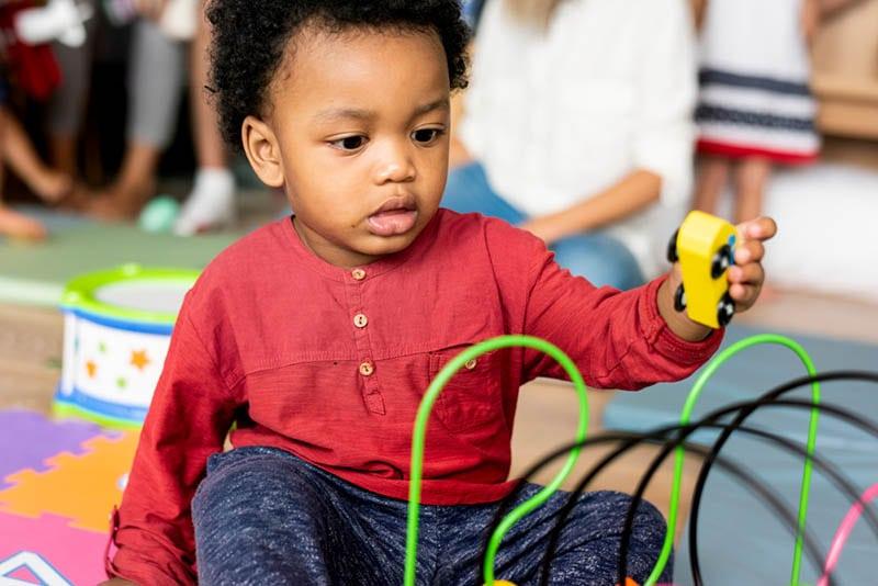 süßer kleiner Junge, der mit Spielzeug im Kindergarten spielt