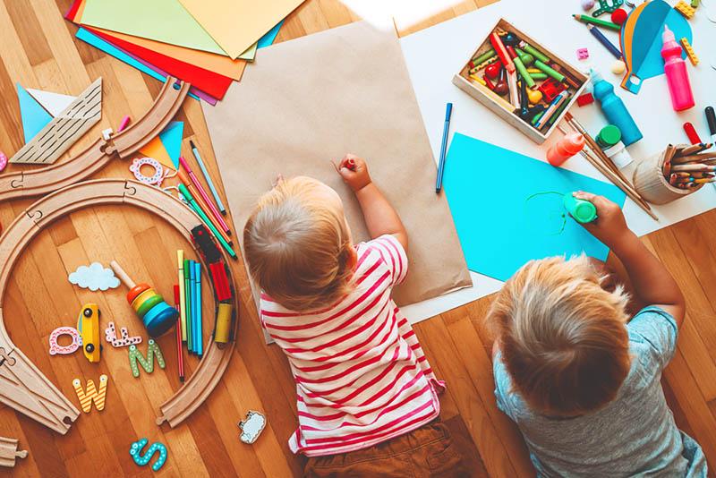 zwei Kinder, die ein Handwerk mit bunten Stiften im montessori Kindergarten zeichnen