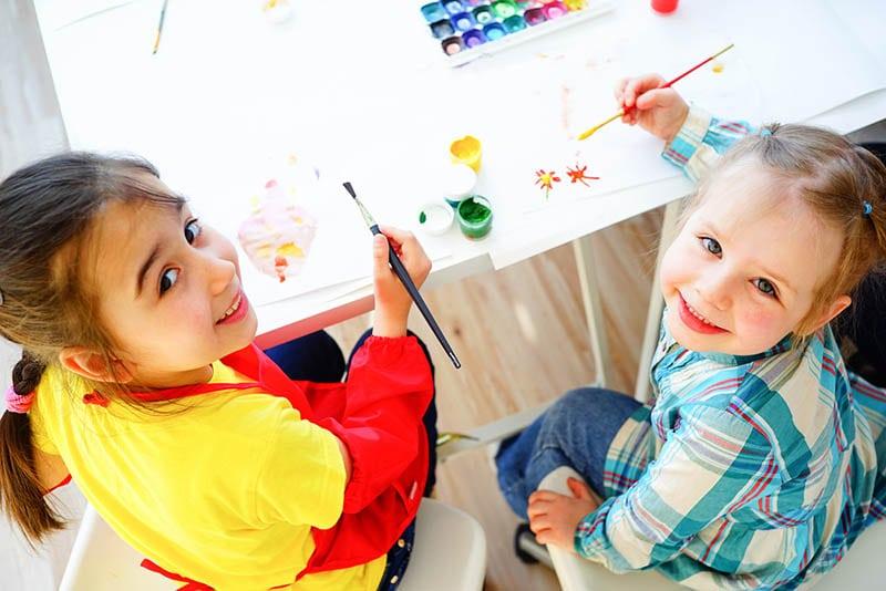 zwei entzückende Mädchen, die Zeichnungen im Kindergarten ausmalen und lächeln