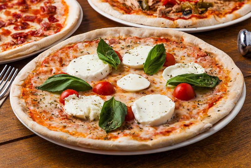 Authentische italienische Pizza mit Mozzarella-Käse, Basilikum und Kirschtomaten, serviert auf einem Teller
