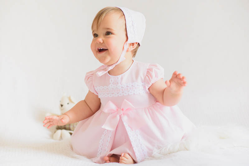 Baby, das rosa Kleid trägt und lächelt