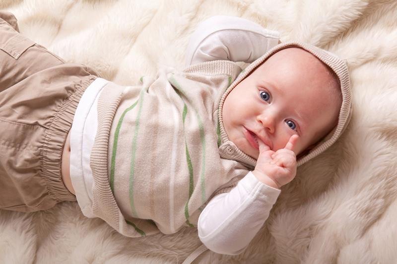 Baby trägt Pullover mit Hut und saugt Daumen auf dem Bett