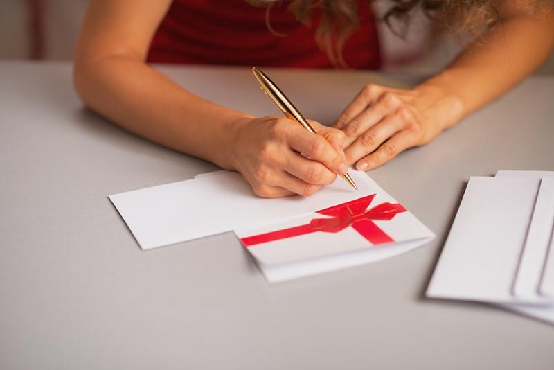 Frau mit lockigem Haar sitzt am Tisch und schreibt einen Brief