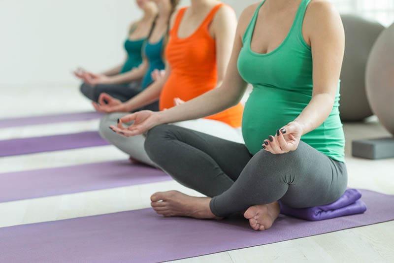 Gruppe von Frauen, die Yoga im Lotussitz nebeneinander machen