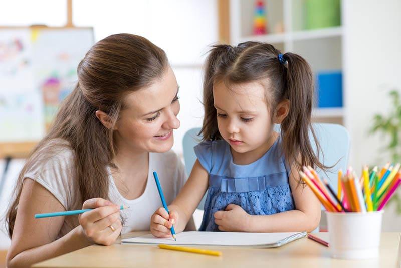 Junge Lehrerin Zeichnung zusammen mit niedlichen kleinen Mädchen im Kindergarten