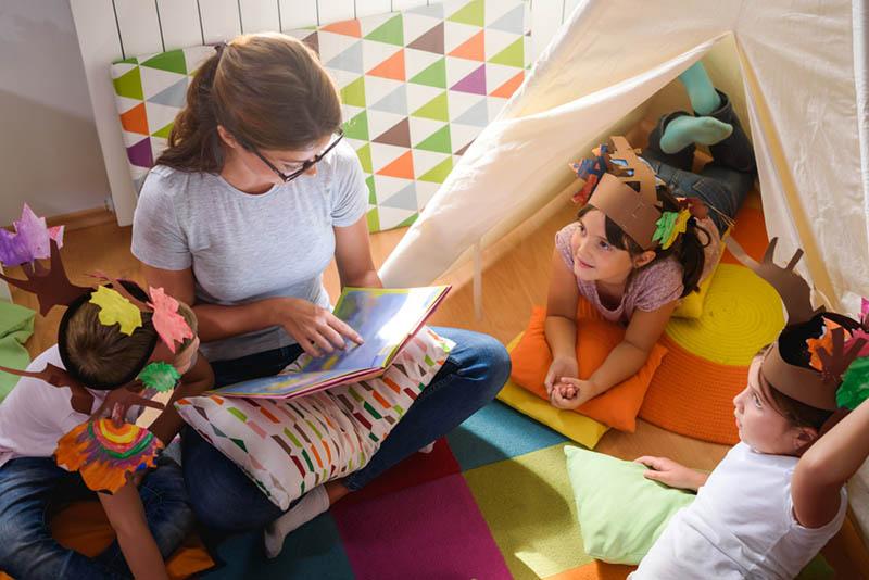Junge Lehrerin liest Kindern auf dem Boden im Kindergarten eine Geschichte vor