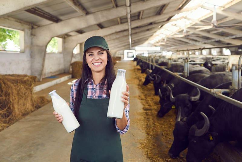 Lächelnde Frau hält zwei Flaschen mit frischer Büffelmilch auf der Büffelfarm
