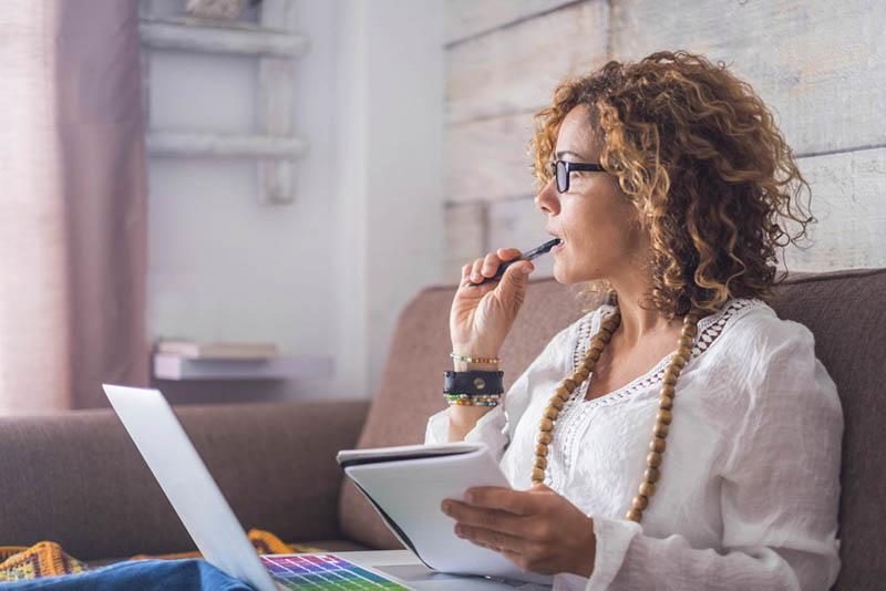 achtsame Frau sitzt auf der Couch mit Laptop im Schoß und einem Stift im Mund