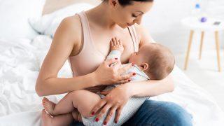 junge attraktive Mutter, die ihr Baby auf dem Bett stillt