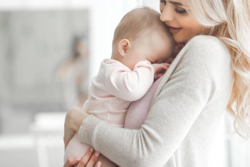blonde hübsche Frau, die schlafendes Baby in den Armen trägt