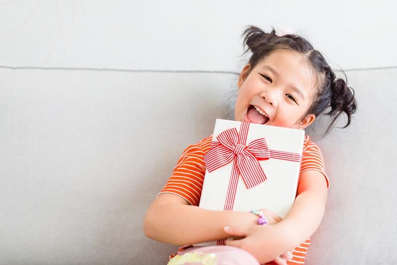 ein süßes kleines Mädchen, das lächelt und ein Geschenk mit beiden Händen hält