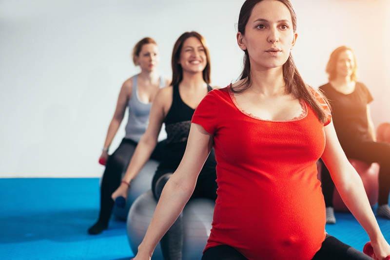 eine Gruppe schwangerer Frauen, die auf Pilatesball sitzen und Gewichte heben