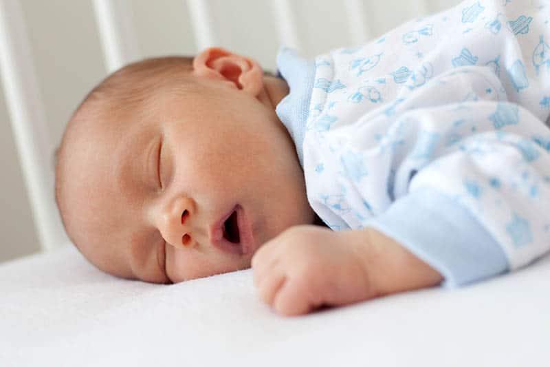 entzückendes neugeborenes Baby, das auf seinem Bauch mit offenem Mund schläft