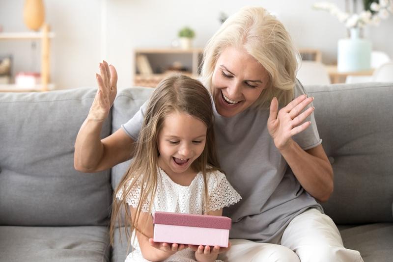 glückliche Großmutter überrascht ihre kleine Enkelin mit Geschenk im Wohnzimmer
