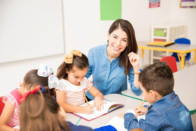 glückliche Lehrerin posiert, während Kinder in einem Notizbuch im Kindergarten schreiben