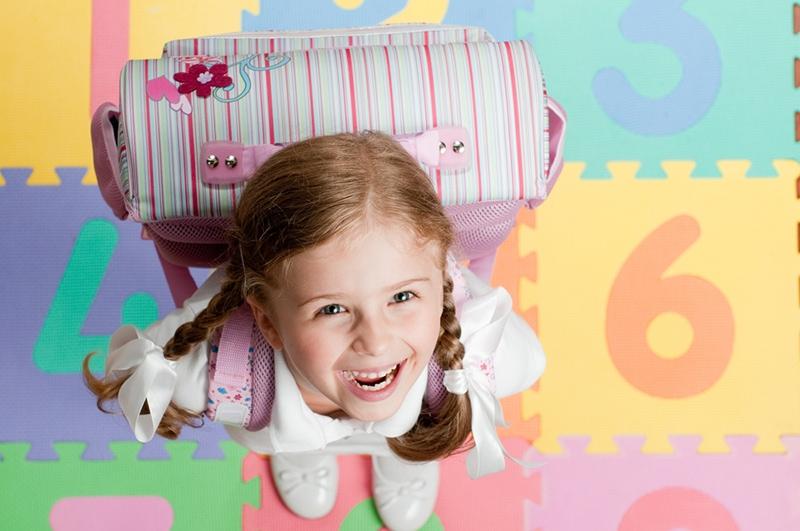glückliches kleines Mädchen mit der großen Schultasche, die oben schaut und lächelt