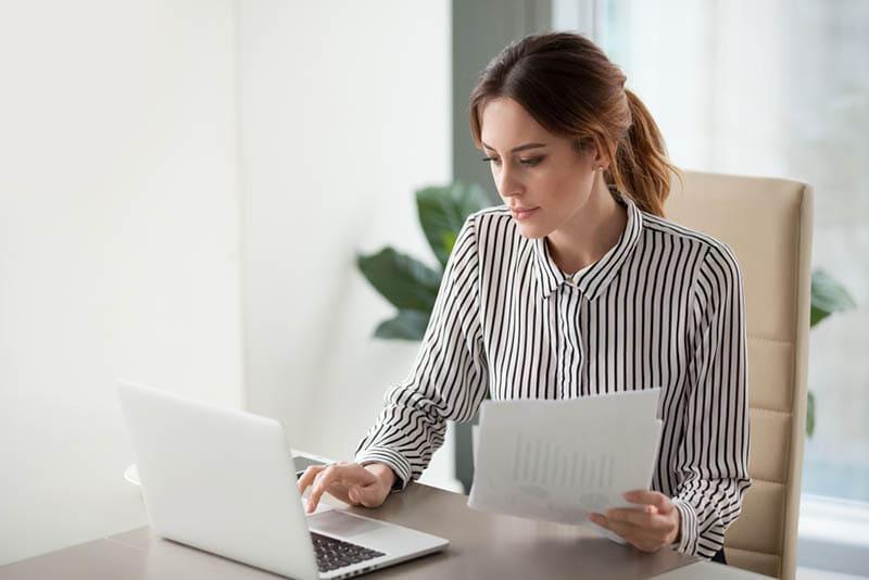 junge Frau sitzt am Tisch und tippt auf dem Laptop mit Papieren in der Hand