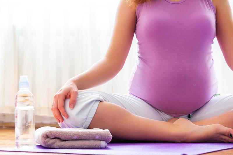 junge schwangere Frau, die in Lotussitz mit Flasche Wasser und Handtuch sitzt