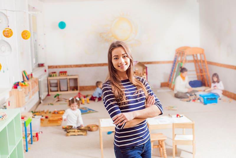 junger lächelnder Lehrer, der im Zimmer posiert, während Kinder auf dem Boden spielen