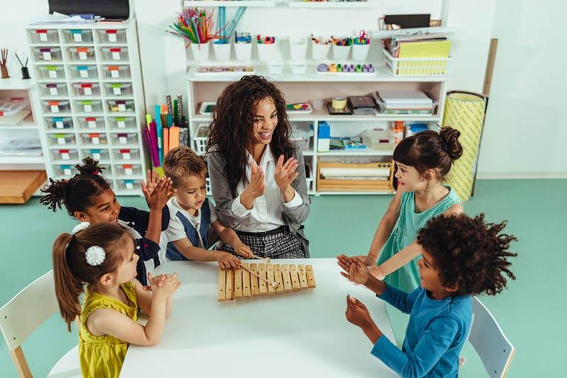 kleiner Junge spielt Musikinstrument und der Lehrer und andere Kinder klatschen mit Händen