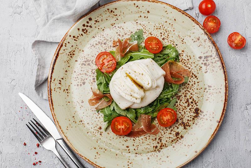 köstlicher Büffelmozzarella-Käse, serviert auf einem Teller mit Salat