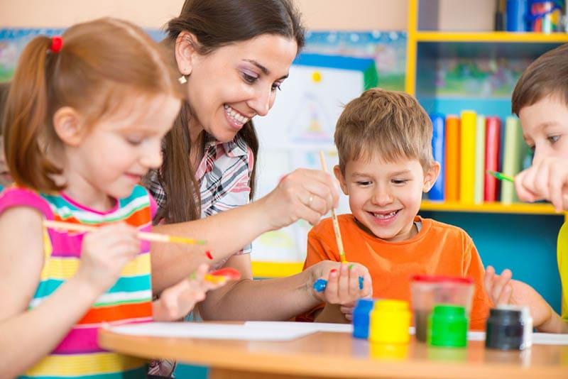lächelnd Lehrer Malerei durch den Tisch mit Kindern im Kindergarten