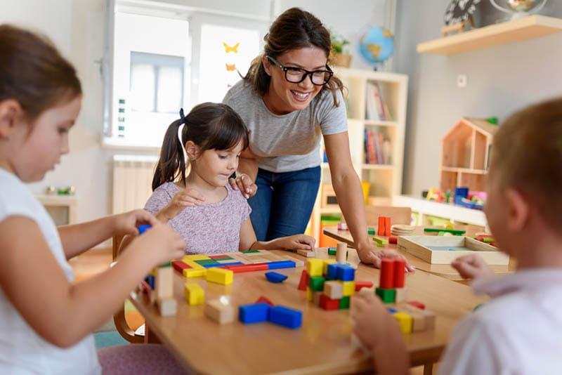 lächelnd Lehrer beobachten, wie Kinder mit Spielzeug im Kindergarten spielen