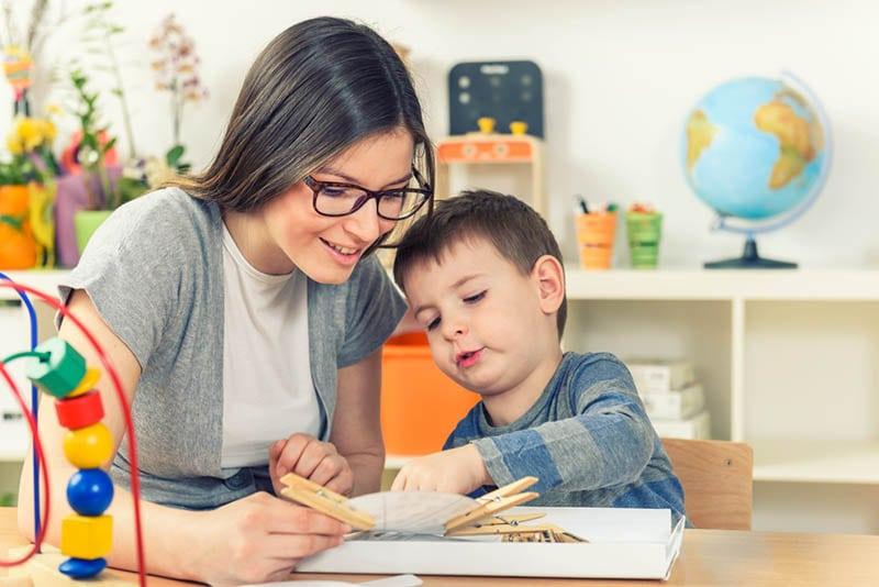 lächelnd Lehrer lernen mit niedlichen kleinen Jungen in den Kindergarten