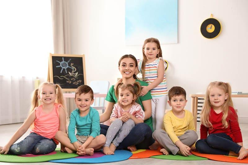 lächelnder Lehrer mit glücklichen Kindern, die auf dem Boden sitzen und posieren