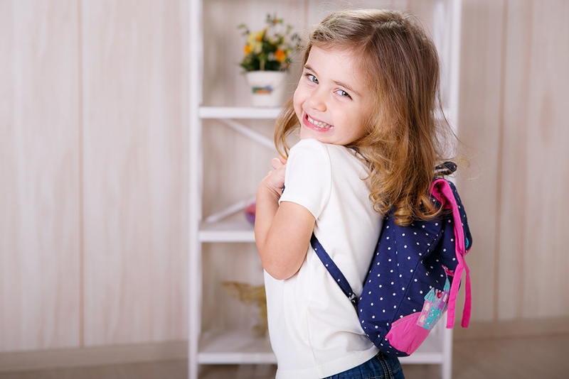 lächelndes kleines Mädchen, das Rucksack trägt und aufwirft