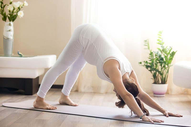 schwangere Frau, die Yoga im gemütlichen Wohnzimmer tut