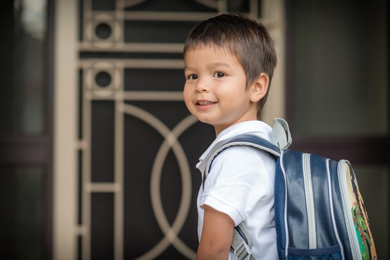 süßer Junge mit Schultasche zur Schule gehen