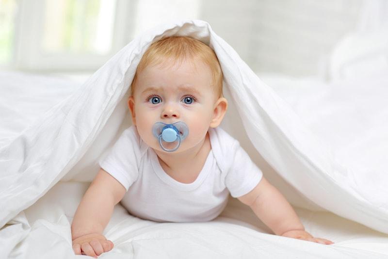 süßes Baby, das unter dem Laken liegt und Schnuller saugt