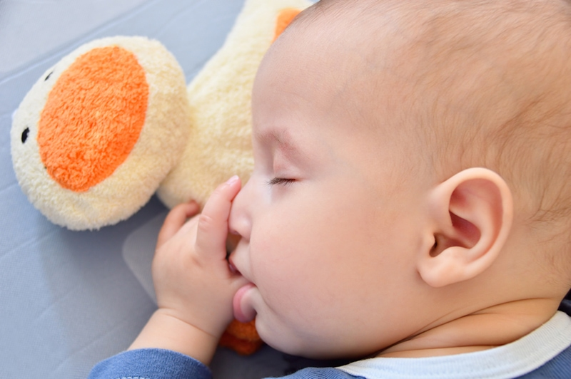 süßes Baby saugt seinen Daumen im Schlaf mit Spielzeug neben ihm