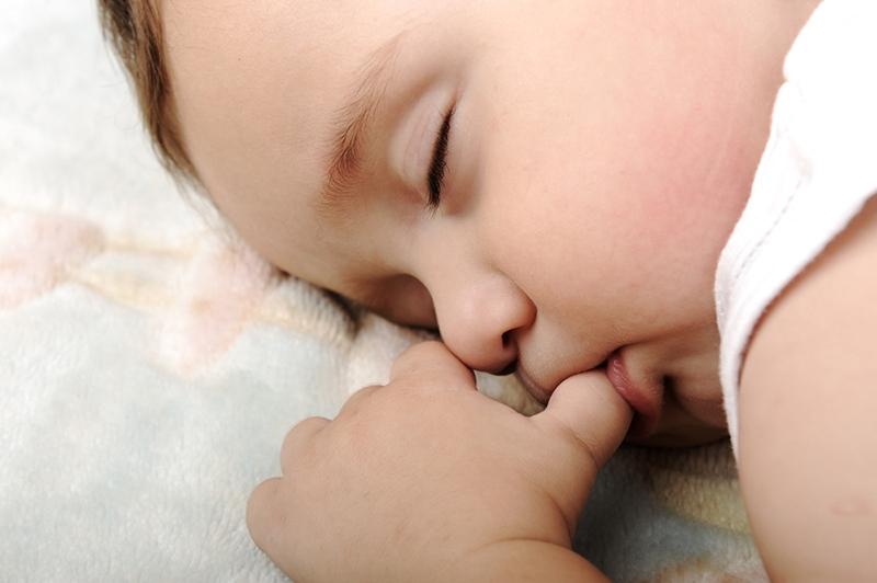 süßes Baby saugt seinen Daumen während des Schlafens
