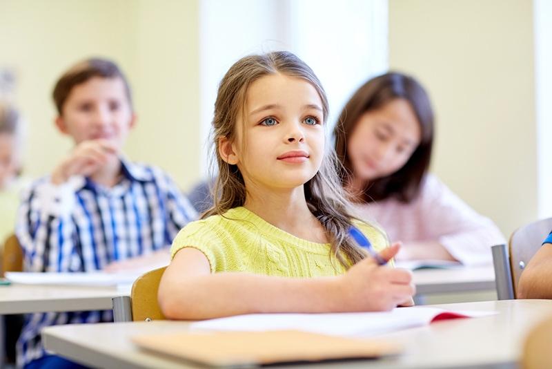 süßes kleines Mädchen mit blauen Augen, das im Klassenzimmer mit Klassenkameraden sitzt
