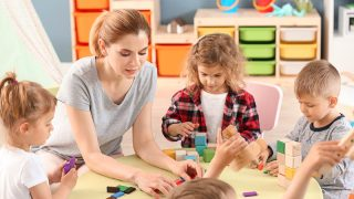 Lehrerin spielt mit Kindern mit Würfeln am Tisch
