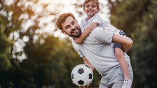 glücklicher Vater, der seinen Sohn mit Fußball auf dem Rücken trägt
