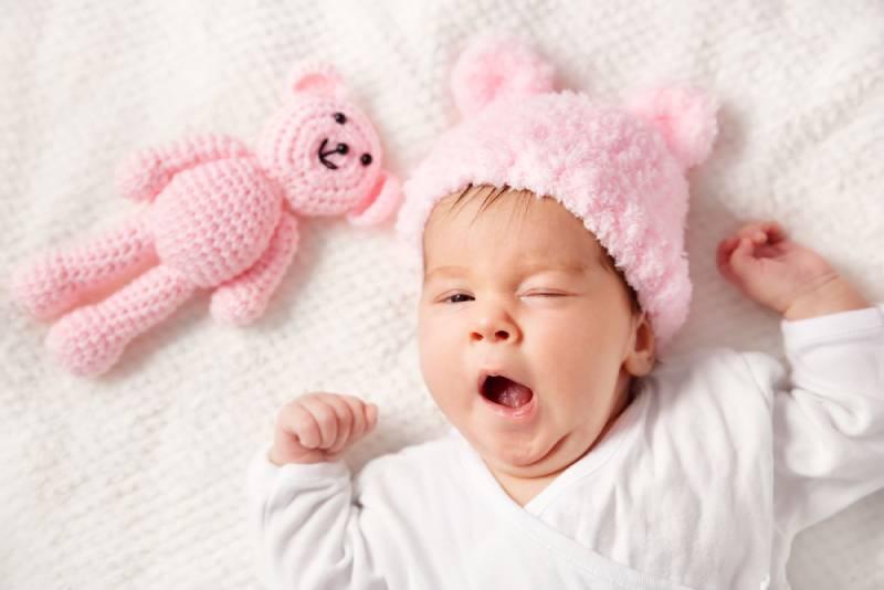 Baby-Mädchen auf dem Bett liegend mit rosa Spielzeug und gähnt