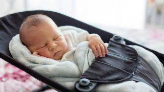 süßes Baby schläft in einer Schaukel