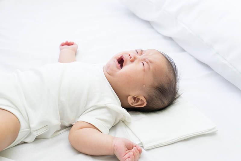 Baby liegt auf dem Rücken im Bett und weint