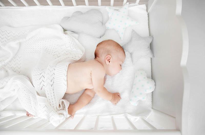 Baby mit weißen Decke bedeckt schlafen fest in Krippe zu Hause