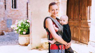 lächelnde junge Mutter, die ihr Baby in einer Trage im Freien trägt
