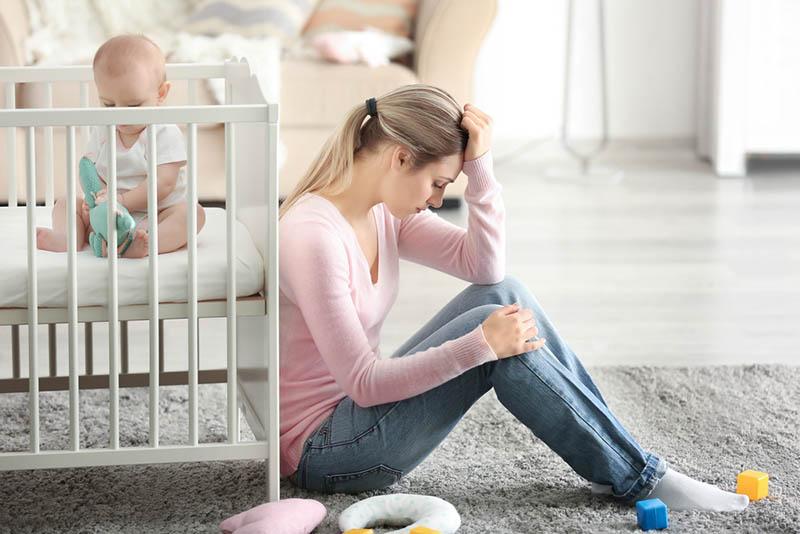 Besorgte Frau sitzt an der Krippe, während das Baby spielt