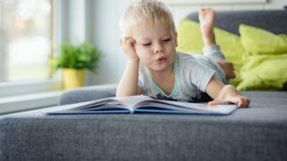 dreijähriger Junge, der auf dem Bauch auf dem Sofa liegt und liest